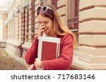 Stock photo student smiling shy woman holding books smiling hiding face with hand long hair casual outfit 717683146