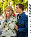 Small photo of Autumn couple walking park. First date in good weather day. Betrayal and forgiveness of girl is crying with handkerchief on outdoor. Man apologizes and gives rose flowers. Guy comforts crying girl.
