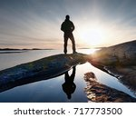 Small photo of Tall backpacker watch clear sunny spring daybreak over sea. Hiker with backpack stand on rocky shore and his figure is mirrored in water pool. Hiker enjoy breathtaking sunrise. Hiking ambition.