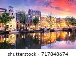 Stock photo sunset city view of amsterdam the netherlands with amstel river 717848674
