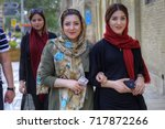 Small photo of Fars Province, Shiraz, Iran - 18 april, 2017: Young Iranian women, dressed in hijab, are walking along a city street with smartphones in their hands.
