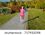 woman running in autumn park ... | Shutterstock . vector #717933298