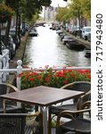 Small photo of alfresco table of a bar near a wagterway canal with boats
