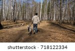 man walks with dog in autumn... | Shutterstock . vector #718122334