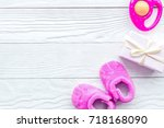 pink baby's bootees on wooden... | Shutterstock . vector #718168090