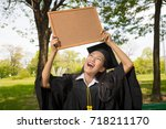 Small photo of Beautiful woman graduating holding empty wooden board and smiling in an academic gown.