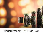 Casino theme. High contrast image of casino roulette, poker game, dice game, poker chips on a gaming table, all on colorful bokeh background.  - stock photo