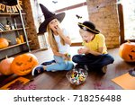 Small photo of Sweets for us! Treat or trick! Very cheerful excited small kids in carnival head wear, with colorful treats, carved pumpkins, fall leaves, enjoying, sittig on browm wooden floor, casual outfits