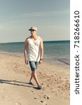 young handsome man on the beach   Shutterstock . vector #718266610