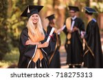 Portrait of young happy joyful graduate in mantle who standing outdoor and keeping diploma in hand and smiling
