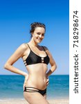 Small photo of Portrait of young woman in black bikini on sand seashore. Attractive young woman in black bikini stands with arms akimbo against the sea looking at camera smiling