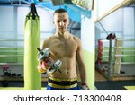 fit shirtless young man lifting ... | Shutterstock . vector #718300408