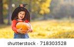 happy child girl with pumpkin... | Shutterstock . vector #718303528