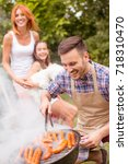 young family having barbecue... | Shutterstock . vector #718310470