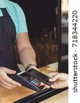 Small photo of Person paying pay through smartphone using NFC technology in outdoor cafe