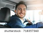 handsome male driver in car | Shutterstock . vector #718357360
