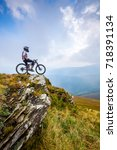 a man stands with a bike on top ... | Shutterstock . vector #718391134