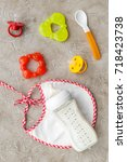 Small photo of bottle with breastmilk and infant formula powdered healthy food, toys and bib on stone background top view