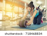 Small photo of using abdominal roller for working out abdominals.