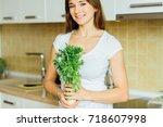 Small photo of Young woman holding green groceries, healthy nutritious balanced diet, isolated indoors home background. Locally sourced food.