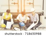 Small photo of Three of engineers are discouraged. Disappointed after unsuccessful work, sitting on floor behind site and hugged their throats. Use effect filter.
