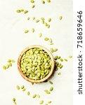 raw pumpkin seeds in wooden... | Shutterstock . vector #718659646