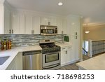 Stock photo beautiful open plan second floor kitchen with traditional style cabinets mosaic backsplash a bar 718698253