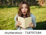 shocked brunette woman sitting... | Shutterstock . vector #718707184