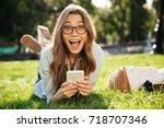 surprised happy brunette woman... | Shutterstock . vector #718707346