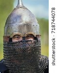 Small photo of The face of an Asian warrior in an eastern helmet, threateningly looking. A stern look. chain armor