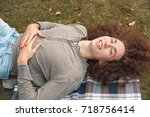 a curly young man lies on the...   Shutterstock . vector #718756414