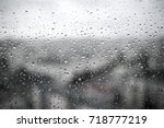 Small photo of Drops of rain on a black dramatic window glass background. Rain in the city. Autunm depression concept image