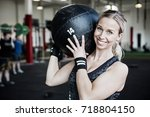 smiling young woman lifting... | Shutterstock . vector #718804150