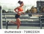 female runner jogging on the... | Shutterstock . vector #718822324