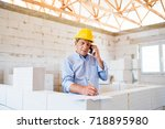 Senior architect with smartphone at the construction site. - stock photo