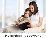 mom and child read book. | Shutterstock . vector #718899940