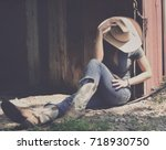 Small photo of Girl in western wear relaxes in shadows of barn, representing agriculture industry in cowboy hat, jeans and cowboy boots.