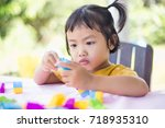 little girl playing with... | Shutterstock . vector #718935310