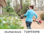 woman using trimmers on hedges... | Shutterstock . vector #718955098