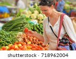 young woman choosing vegetables | Shutterstock . vector #718962004