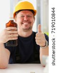 Small photo of Arm of drunken worker in yellow helmet show OK gesture or confirm sign with thumb up closeup.