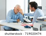 sad older worker and younger... | Shutterstock . vector #719020474