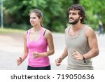 couple running in a park.... | Shutterstock . vector #719050636