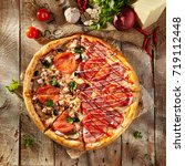 Small photo of Pizza in half with chicken and mushrooms and greens, on other - with ham and sauce. On rustic wooden background with fresh vegetables. Top View
