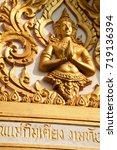 Small photo of Pattaya, Thailand - March 25, 2016: Golden figure of Buddha god carved on an Asian Buddhist shrine. Beautiful ornamental decoration with some religious text inscribed on a Thai temple