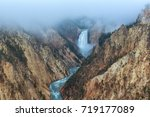 Morning fog lifts above the Lower Falls of the Yellowstone River in Wyoming, USA