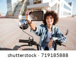 pleased curly woman sitting on... | Shutterstock . vector #719185888