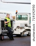 worker leaning on trailer at...   Shutterstock . vector #719192950