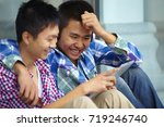 two boy sitting outside with... | Shutterstock . vector #719246740