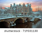 Stock photo snowy amsterdam in the netherlands in winter at sunset 719331130